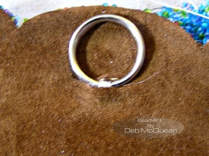 after trimming the beaded felt and cutting a piece of leather for backing I added a ring for hanging